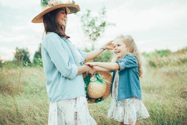 若い母親と娘の緑の草の背景