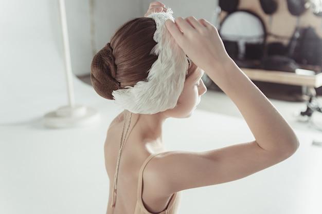 Красивая маленькая балерина в повязке на голове белого лебедя