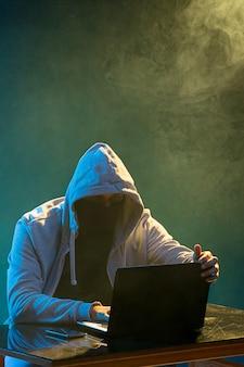 フード付きのコンピューターハッカーがラップトップで情報を盗む