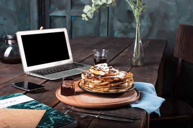 ノートパソコンとジュースとパンケーキ。健康的な朝食