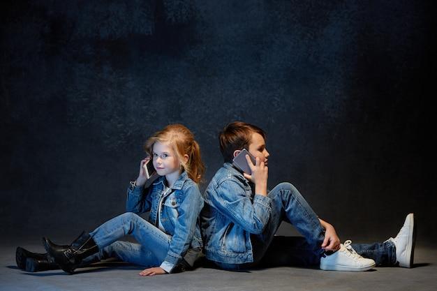 座ってジーンズでポーズをとる子供たち