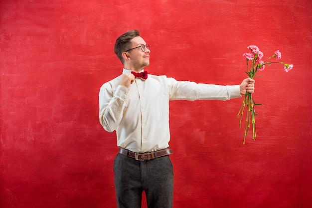 花を持つ若い美しい男