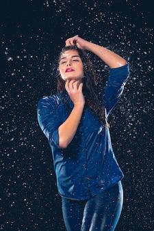 雨のしぶきの下で若い美しい女性