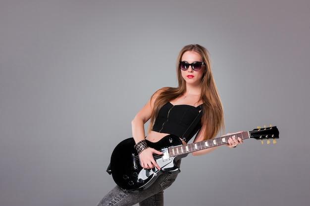 Красивая девушка играет на гитаре