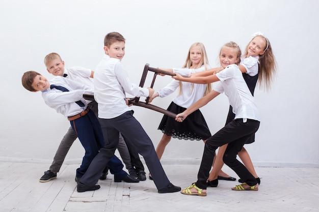 椅子の綱引きをしている子供たち-女の子対男の子