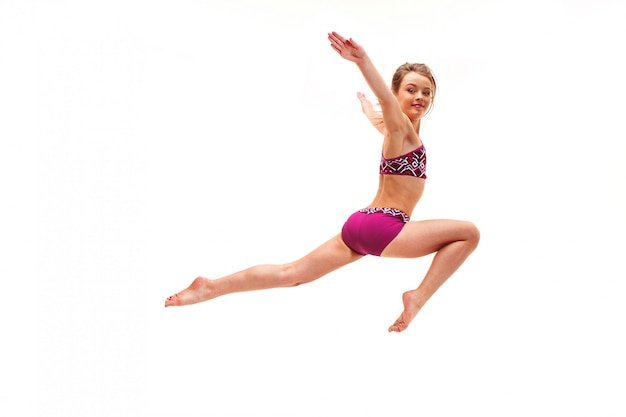 Девушка подросток делает гимнастические упражнения, изолированные на белой стене