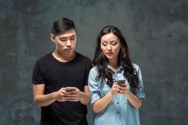Азиатские молодые пары используя мобильный телефон, портрет крупного плана.