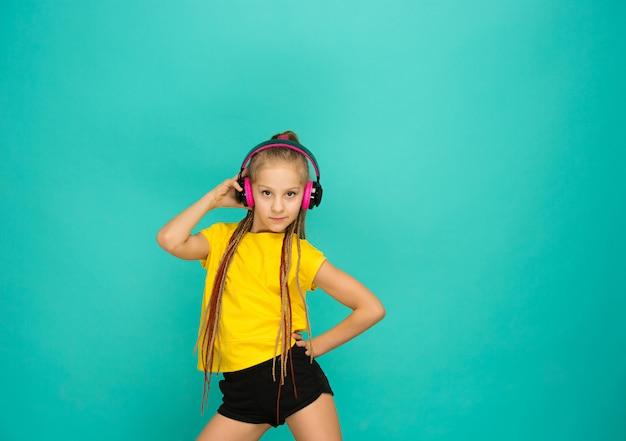 水色の壁にヘッドフォンで魅力的な女の子