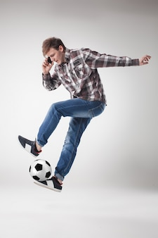 Портрет молодого человека с умным телефоном и футбольным мячом