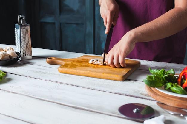 Крупным планом рука шеф-повара пекаря, делая пиццу на кухне