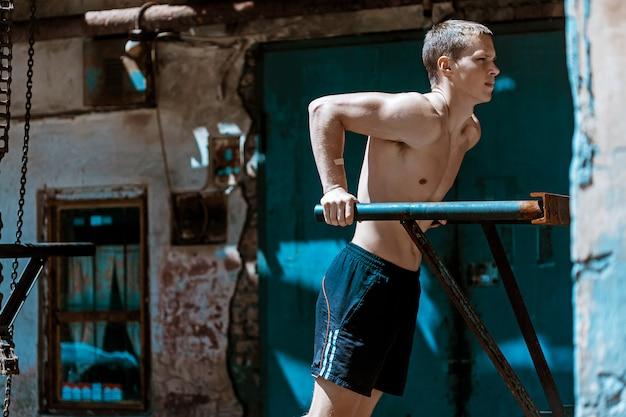 筋肉質の男が鉄の鎖に対してプッシュアップを行う