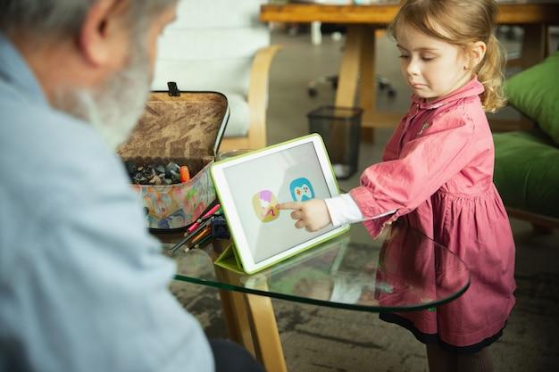 祖父と家で一緒に遊ぶ子供。幸福、家族、関係、教育の概念。