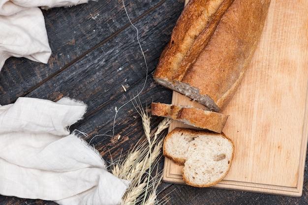 木製のテーブルで素朴なパン。フリーテキストスペースを持つ暗い木質背景。