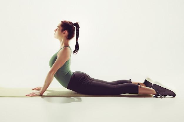 白いスタジオ背景にジムでストレッチ体操を行う若いスリム美人