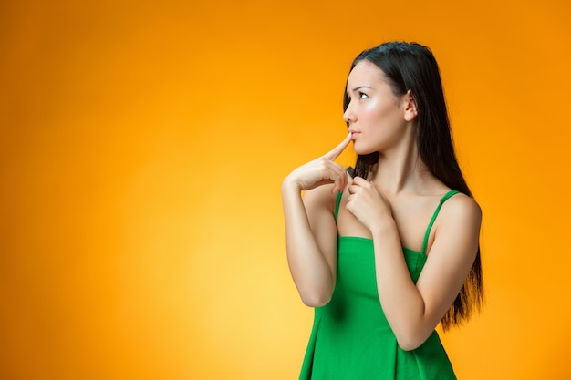 Думая китайская девушка на желтом фоне