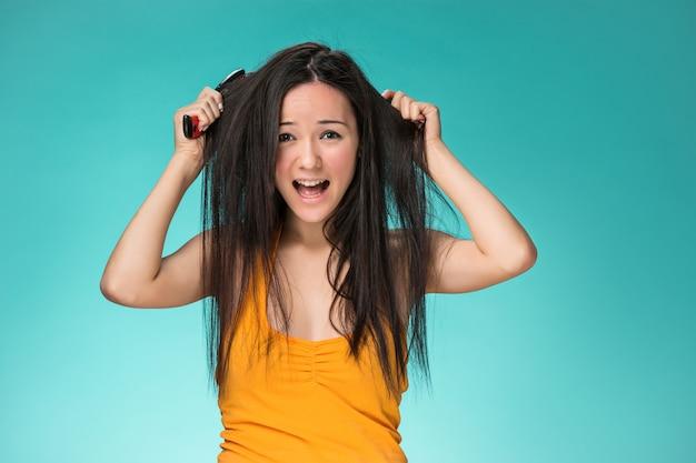 悪い髪を持つ欲求不満な若い女