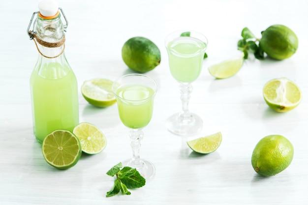 Домашний лаймовый ликер в стакане и свежие лимоны и лаймы на белом