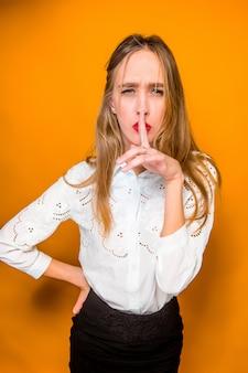 オレンジ色の背景に深刻な欲求不満の若い美しいビジネス女性