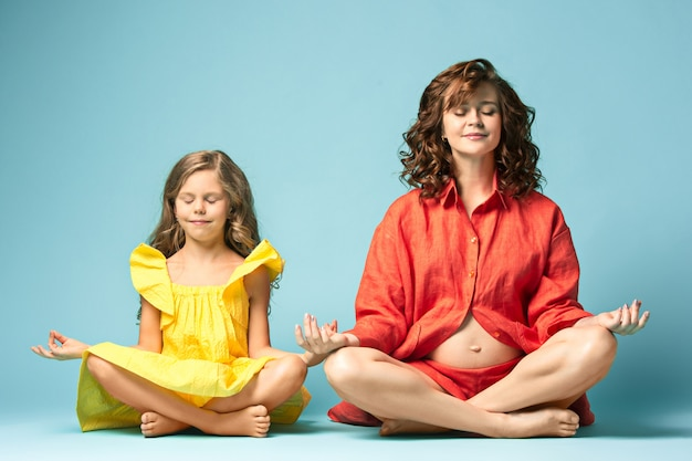 Беременная мать с дочерью подростка. семейный студийный портрет на синем фоне