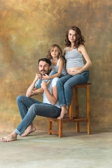 Беременная мать с дочерью подростка и мужем. семейный студийный портрет на коричневом фоне