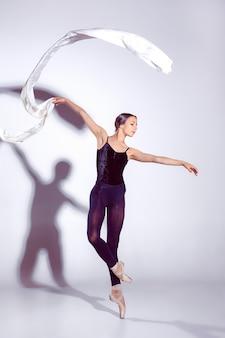 Балерина в черном платье позирует на пальцах ног, фон студии.