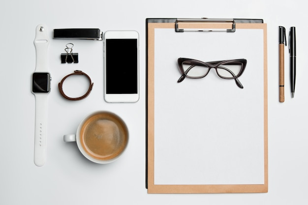 Стол офисный стол с чашкой, принадлежности, телефон на белом