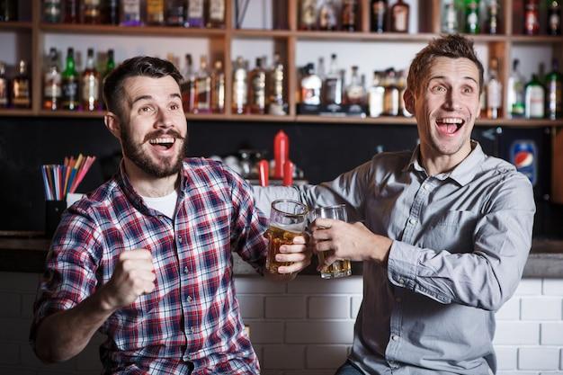 バーでサッカーを見ているビールを持つ若者