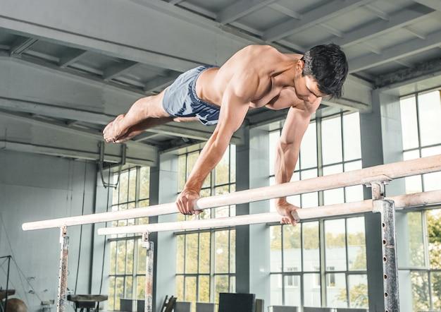 Мужской гимнаст выполняет стойку на руках на брусьях