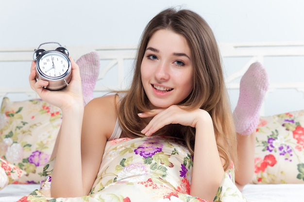 目覚まし時計が付いているベッドで若い女性