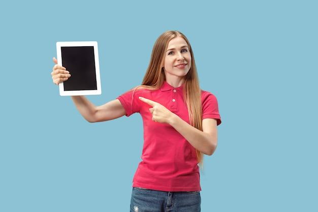ノートパソコンの分離された壁の空白の画面を示す自信を持ってカジュアルな女性の肖像画