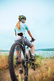 Молодая девушка езда на велосипеде снаружи