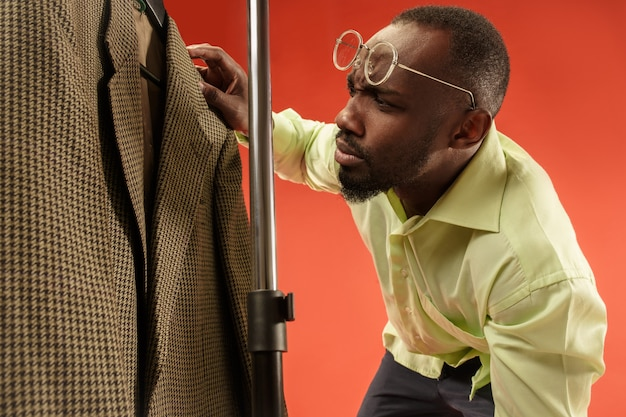 Красивый мужчина с бородой, выбирая рубашку в магазине