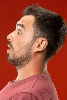 赤に分離されて驚いて探している若い魅力的な男