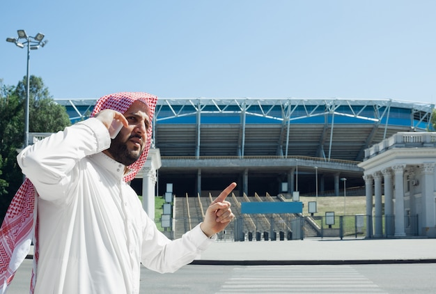 豊かなアラビア人が街で不動産を買う笑顔