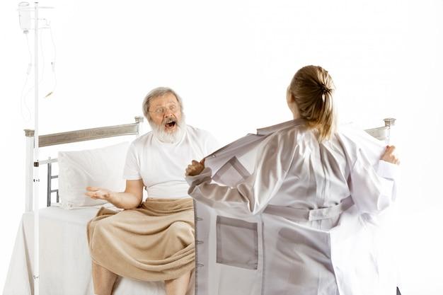 白で隔離される病院のベッドで回復する老人