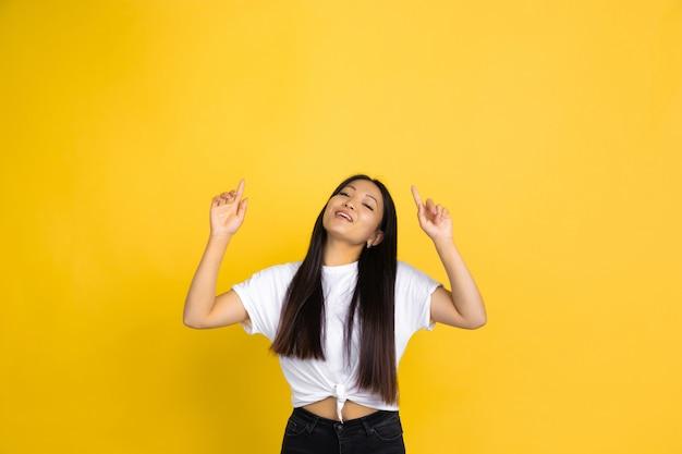 黄色の壁に分離された若いアジアの女性の肖像画