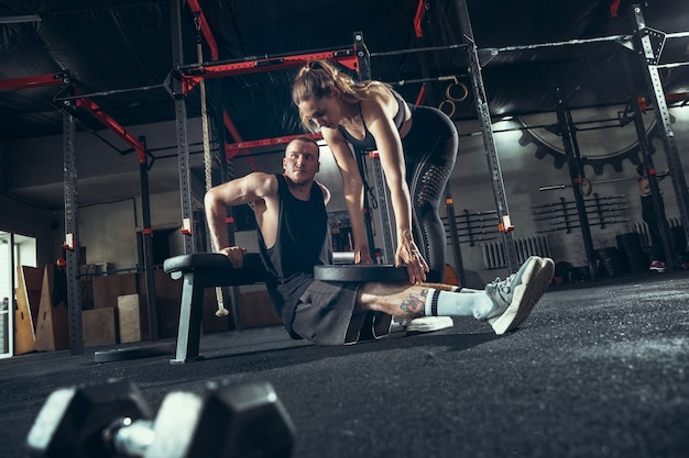 Атлетик мужчина и женщина с гантелями