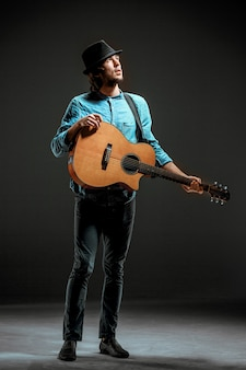 暗い壁にギターで立っているクールな男