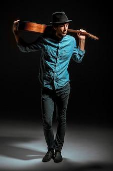 Крутой парень стоял с гитарой на темной стене