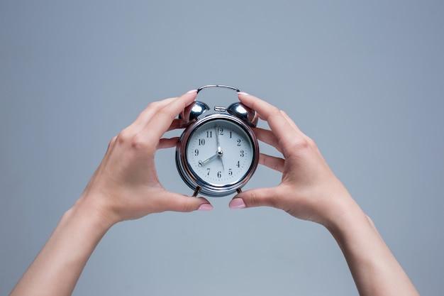 古いスタイルの目覚まし時計を保持している女性の手