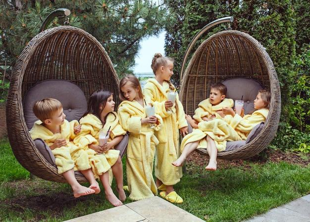 屋外でミルクセーキを飲む子供たち
