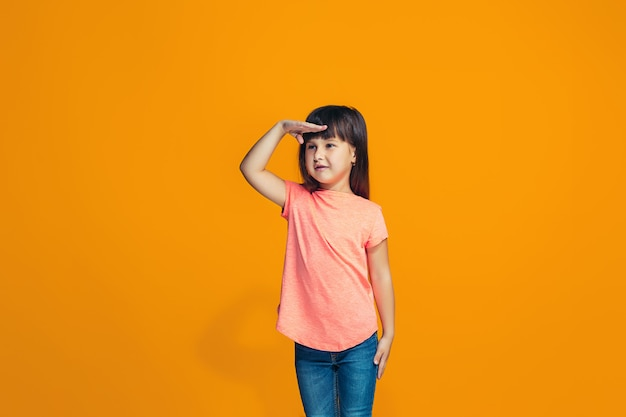 Счастливая девушка стоит и улыбается на оранжевой стене