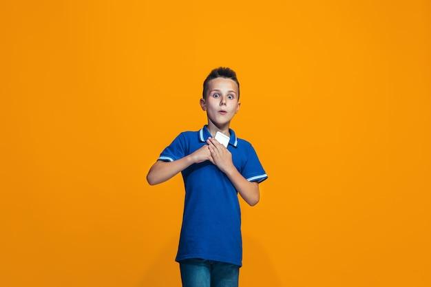 立っているとオレンジ色の壁に笑みを浮かべて幸せな少年
