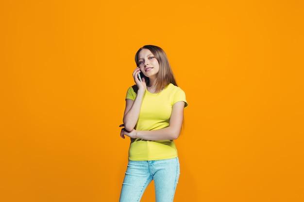 立っているとオレンジ色の壁に笑顔幸せな十代の少女