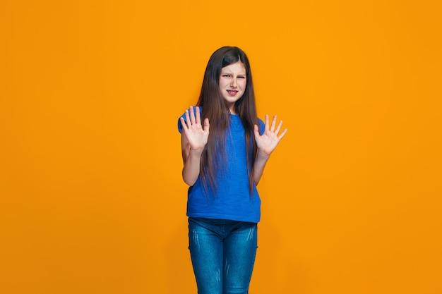 オレンジ色の壁に何かを拒否する疑わしい物思いにふける少女