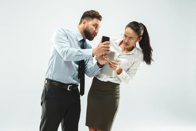 怒っているビジネスマンおよび彼の同僚のオフィス