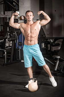 Мускулистый парень культурист делает упражнения с весом в тренажерном зале