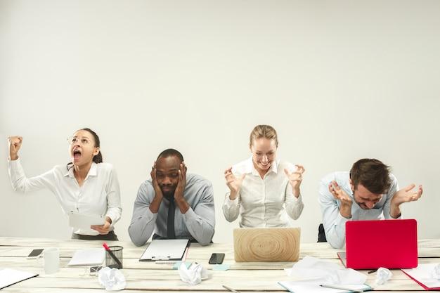 Молодые мужчины и женщины сидят в офисе и работают на ноутбуках. концепция эмоций