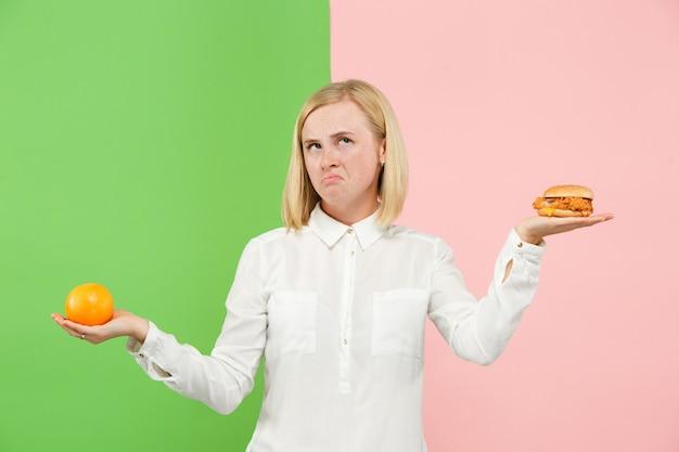 ダイエット。ダイエットのコンセプトです。健康食品。果物と不快なファーストフードの間を選択する美しい若い女性