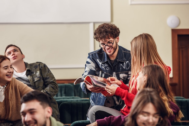 Группа веселых счастливых студентов, сидящих в лекционном зале перед уроком